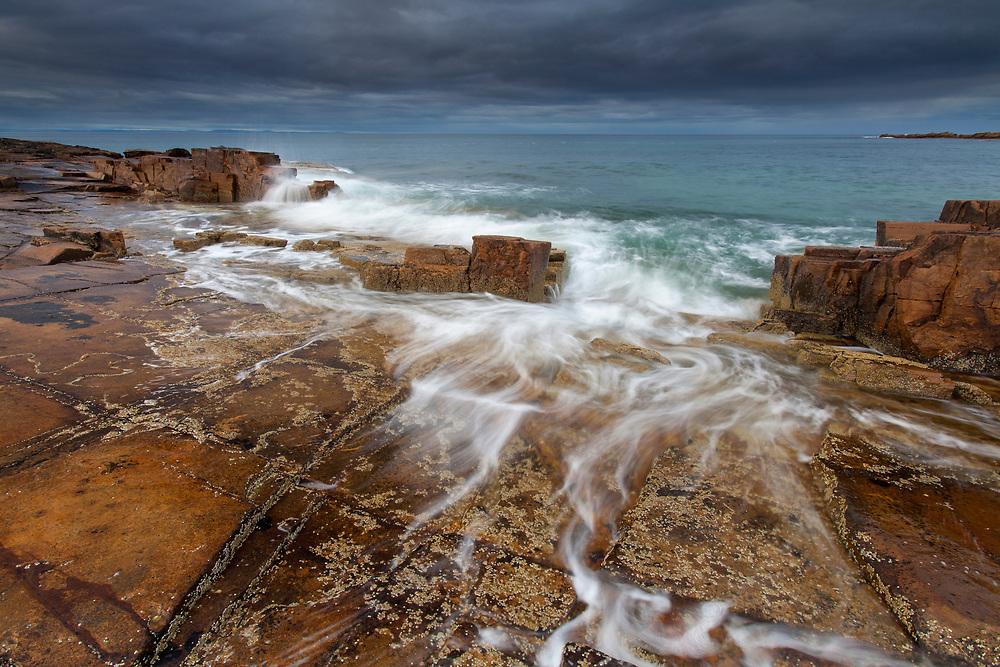 Waves washing over snadstone rocks, Hopeman, Moray, Scotland