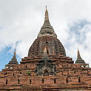 BAGAN, Myanmar - Naga Yon Hpaya Temple, one of thousands of stupas on the plain of Bagan, features ornate stucco work and painting inside and is in the process of being renovated. It has dark internal corridors with strategically placed windows that capture the sun to shine light on the main Buddha statue as well as various statues in alcoves lining the corridors.