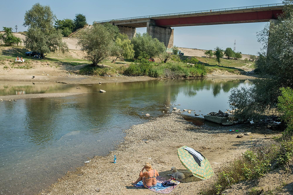 A woman sunbathes next to the Arges River, near a bridge which serves one of the main gates to the city. The sandy banks are popular in the summer when low waters release them from the beneath the water.