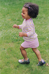 Young girl running on grass in park smiling,