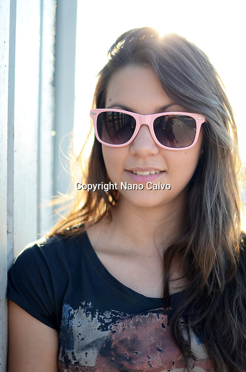 Cute young woman wearing pink sunglasses
