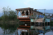 At dusk, the only activity on Dal Lake are the birds gliding through the still water past an empty houseboat.