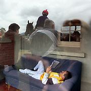 A jockey, without a ride in the next race, relaxes outside the jockey's room as his colleagues mount their horses in the mounting yard during a day at the Races at the Gore Race Meeting, Gore, Southland, New Zealand. 18th December 2011. Photo Tim Clayton