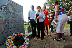 29 August 2013. Lower 9th Ward, New Orleans, Louisiana.<br /> Hurricane Katrina memorial 8 years later. <br /> Former councilwoman Cynthia Willard Lewis holds a rose as Sherlyn Green is comforted at the official memorial in remembrance of the day Hirricane Katrina swamped the community.<br /> Photo; Charlie Varley