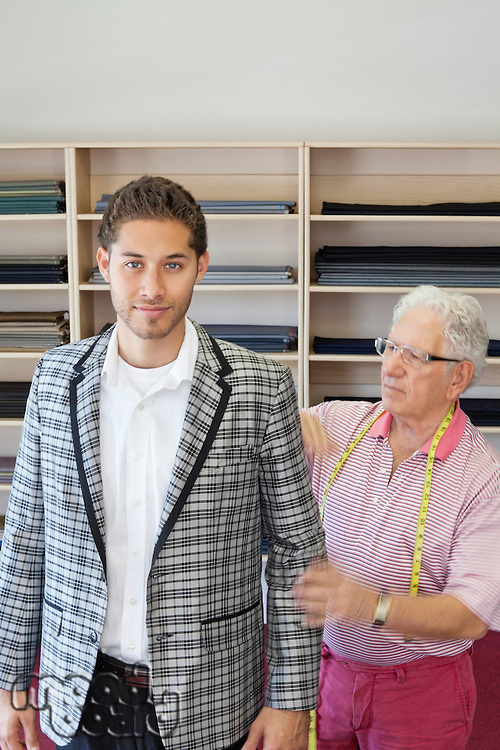 Portrait of young man having custom made suit in tailor's shop