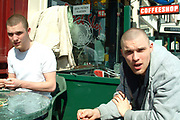 Two brothers sitting outside a coffee shop, one smoking a spliff, one rolling the next one, Amsterdam, Netherlands, 2000's