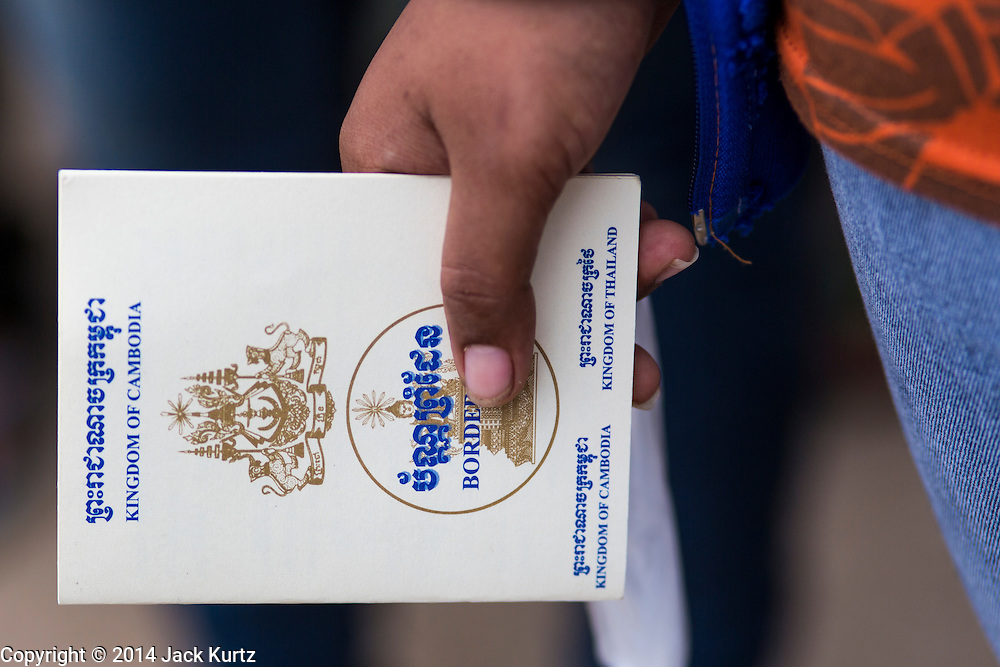 09 JULY 2014 - ARANYAPRATHET, SA KAEO, THAILAND: A Cambodian migrant worker clutches his border crossing permit at the Thai Immigration One Stop Service Center in Aranyaprathet on the Thai-Cambodian border. More than 200,000 Cambodian migrant workers, most undocumented, fled Thailand in early June fearing a crackdown by Thai authorities after a coup unseated the elected government. Employers have been unable to fill the vacancies created by the Cambodian exodus and the Thai government has allowed them to return. The Cambodian workers have to have a job and their employers have to vouch for them. The Thai government is issuing temporary ID cards to allow them to travel openly to their jobs. About 800 Cambodian workers came back to Thailand through the Aranyaprathet border crossing Wednesday. The Thai government has opening similar service centers at three other crossing points on the Thai-Cambodian border.    PHOTO BY JACK KURTZ