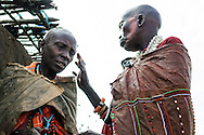 One Maasai woman paints the face of another with red ochre, during a circumcision ceremony.