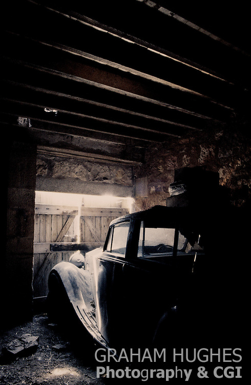 Classic Old Car in Barn with luggage on roof.