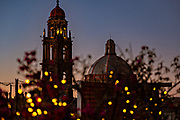 Colorful sunset and fairy lights decorate the view of the bell tower and dome of the San Francisco church in the historic city center of San Miguel de Allende, Mexico.