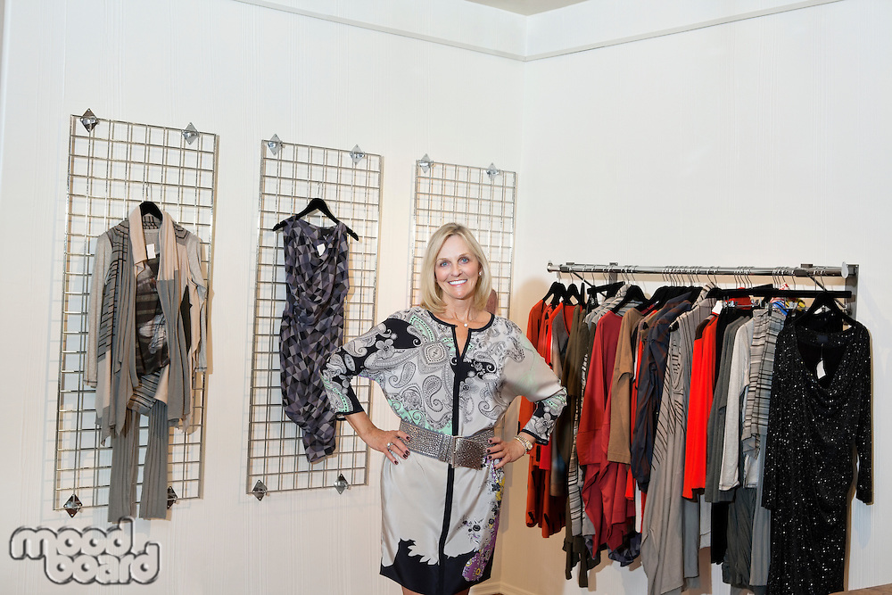Portrait of a happy senior woman standing with hands on hips in fashion boutique