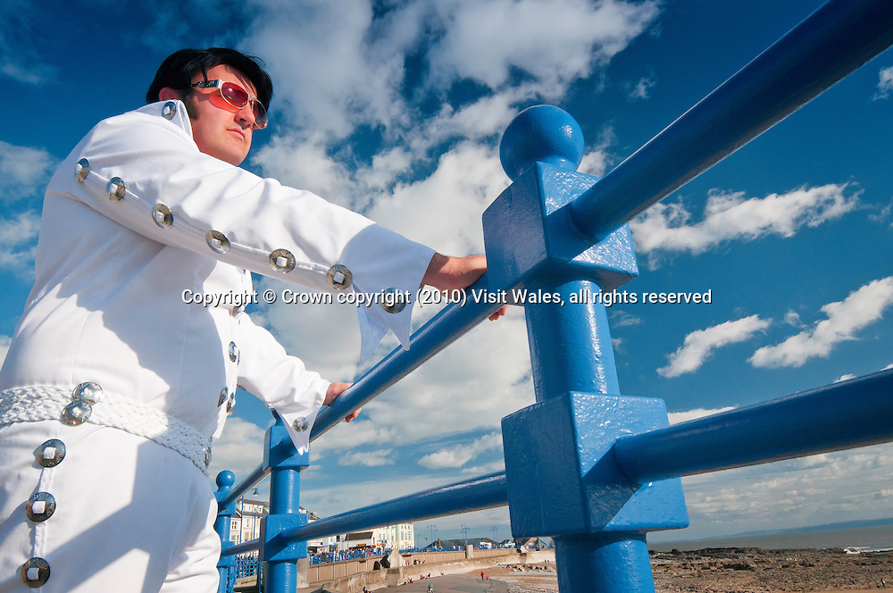 Elvis tribute act / impersonator standing on seafront / promenade<br /> Porthcawl<br /> Bridgend County<br /> Events
