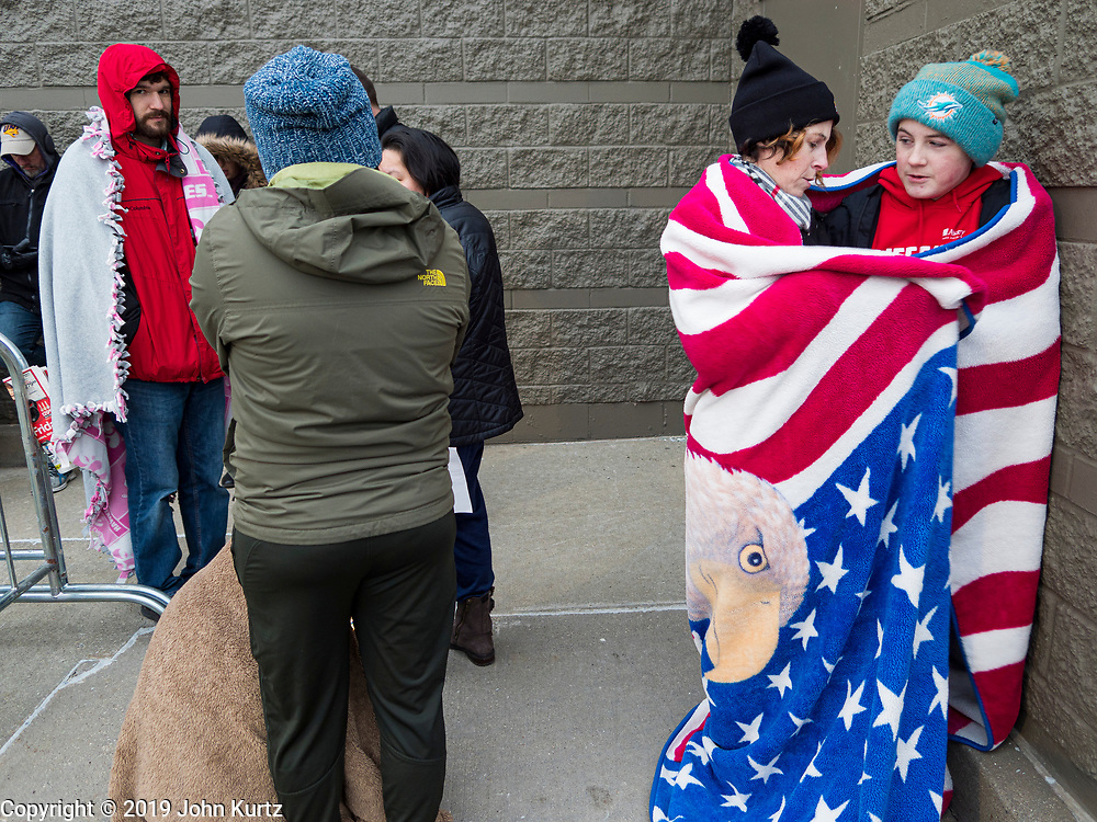 """28 NOVEMBER 2019 - ANKENY, IOWA: COURTNEY POUS-OJEDA and her son XAVIER POUS-OJEDA share a blanket to stay warm while they wait for the Target store in Ankeny, Iowa, top open. """"Black Friday"""" is the unofficial start of the Christmas holiday shopping season and has traditionally thought to be one of the busiest shopping days of the year. Brick and mortar retailers, like Target, are facing increased pressure from online retailers this year. Many retailers have started opening on Thanksgiving Day. Target stores across the country opened at 5PM on Thanksgiving to attract shoppers with early """"Black Friday"""" specials.       PHOTO BY JACK KURTZ"""