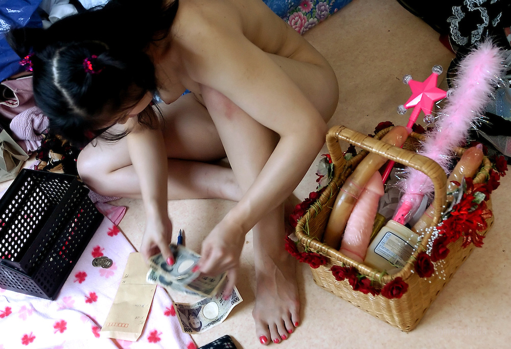 A stripper counts her tip backstage in Tokyo, Japan.