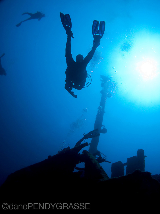 Scuba divers float above the wreck of the El Aguila in Roatan, Honduras.