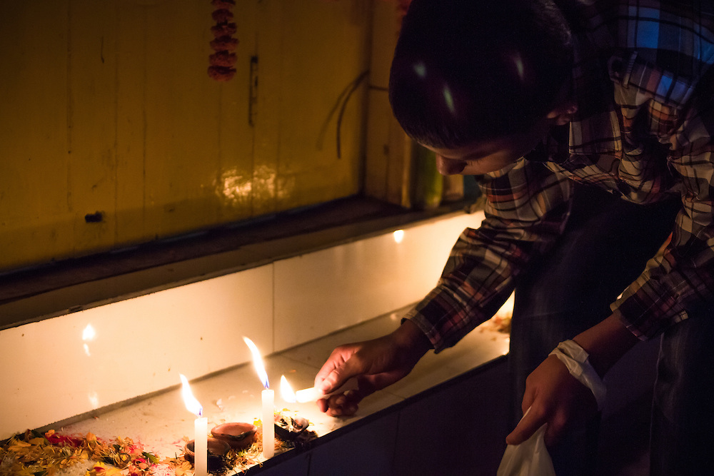 A young hindu boy lighting candles during the Festival of Lights (also known as Deepavali, Diwali or Tihar). Bhaktapur, Kathmandu, Nepal.