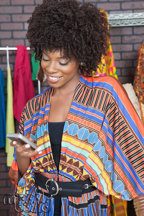 African American female fashion designer reading text message on cell phone