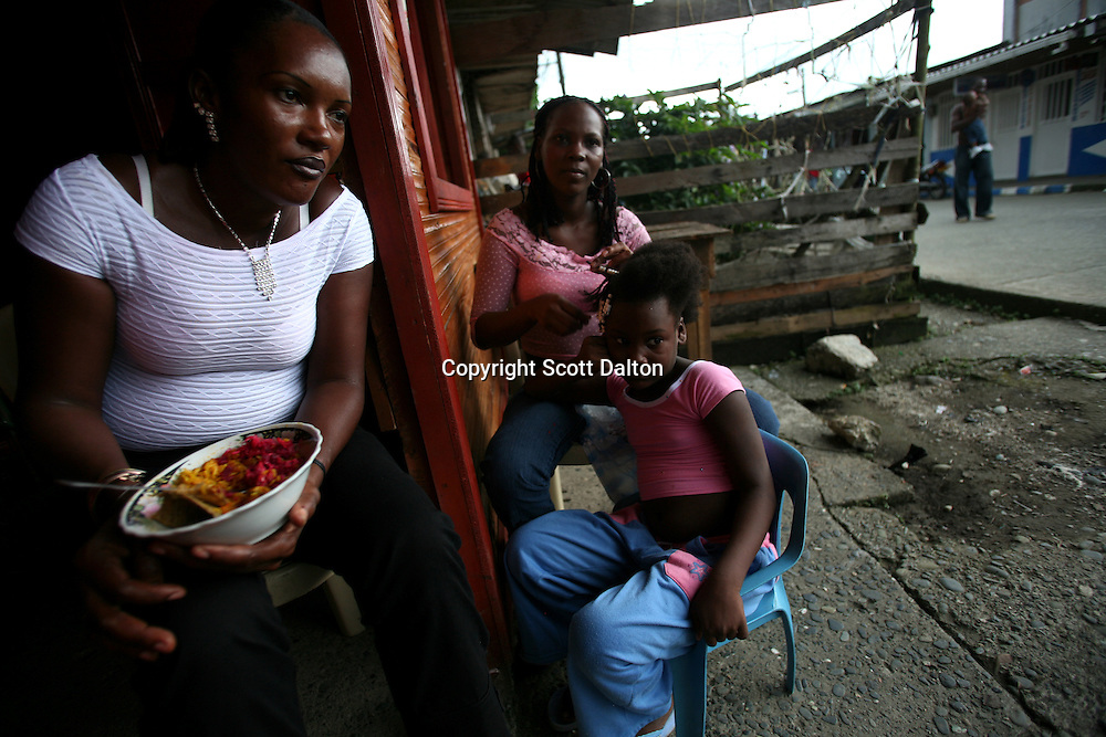 A family sits outside their house as a young girl gets her hair done in Lleras, a poor barrio in Buenaventura, on the Pacific Coast of Colombia, on Sunday, May 13, 2007. Buenaventura is in the midst of a spree of violence over control of drug shipments from the poor barrios in the city. Many of the neighborhoods have a strong presence of FARC militias that control most of the drug trade in the city. (Photo/Scott Dalton)