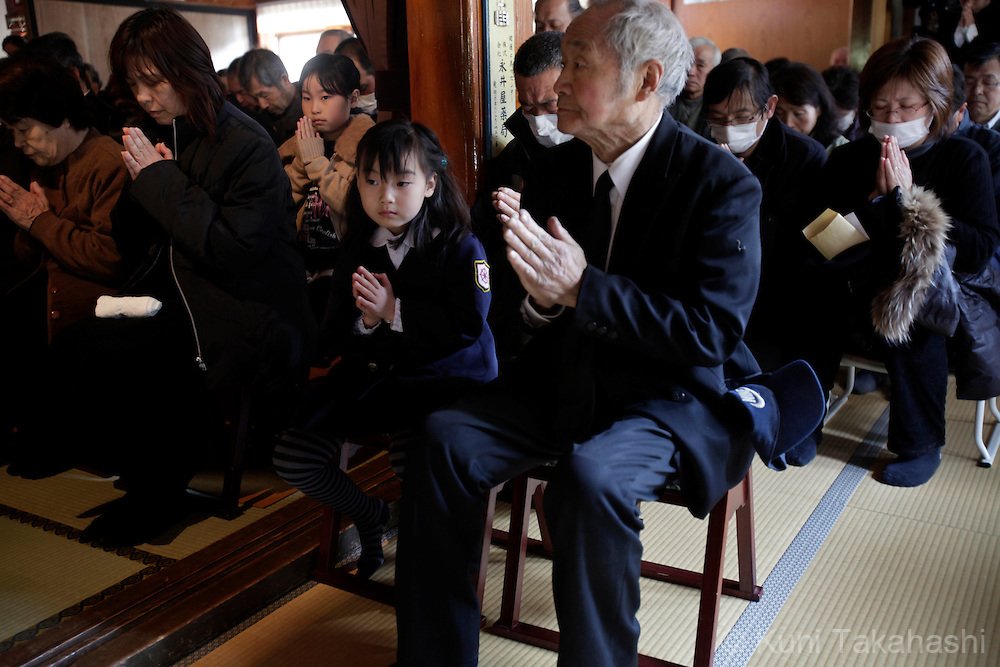 Mourners pray at temple during mass-memorial service for the victims at a temple in MInamisanriku, Miyagi, Japan on March 30, 2011 after massive earthquake and tsunami hit northern Japan. More than 20,000 were killed by the disaster on March 11.<br /> Photo by Kuni Takahashi