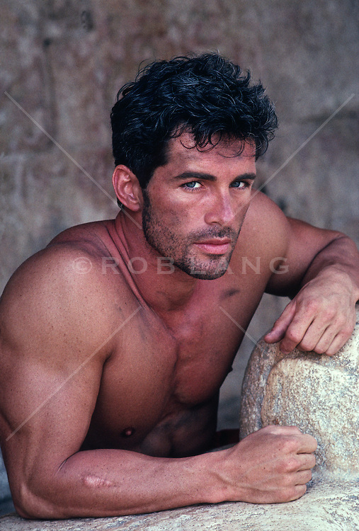 Portrait of a shirtless man leaning on rock