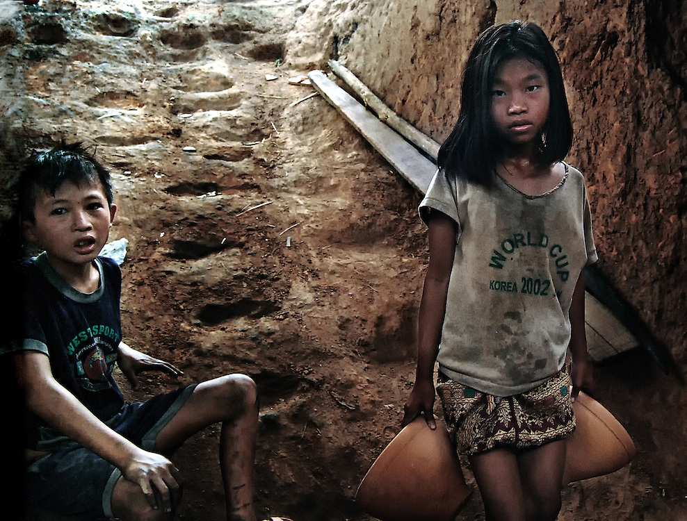 Children load an underground Kiln with pots in Luang Prabang, Laos.
