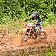 Medium shot of motocross racer splattering mud from a muddy trail during an outdoor race in Belmopan, Belize.