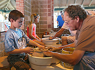 Cole Lennette (from left), 8, of Cedar Rapids works on a clay pot with John MacDonald, a Ceramics Center volunteer, during the 20th Annual Marion Arts Festival at City Square Park in Marion on Saturday, May 19, 2012. (Stephen Mally/Freelance)