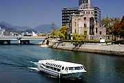 A  tourist boat glides past the A-Bomb Dome in Hiroshima, Japan. The A-Bomb Dome is the skeletal ruins of what was, before the world's first nuclear attack on Aug. 6 1945,  the city's Industrial Promotion Hall. Although the building was the closest to the hypocenter of the nuclear bomb, its basic structure remained standing and has been preserved in the state it was found after the bombing.