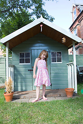 Little girl posing in front of a Wendy house in the garden,