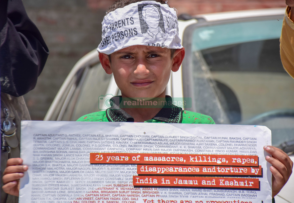 April 28, 2018 - Srinagar, Jammu & Kashmir, India - A small boy holds a placard during a protest of Association of parents of  Disappeared persons (APDP) In Press Enclave Srinagar Summer Capital Of Indian Kashmir on Saturday..Scores of members Association of Parents of Disappeared Persons (APDP) on Saturday staged a silent protest in Press Enclave Srinagar against the human rights violation in Kashmir.The protesters including men, women assembled at Srinagar's Press Enclave and staged silent protest and demanded government to find out their beloved ones who are disappeared since years.The association members were carrying the banners and placards reading 'stop crime against humanity, what lies beneath.' According to APDP, More than 8000 Kashmiris are disappeared since the inception of armed conflict in 1989 in Jammu and Kashmir. (Credit Image: © SOPA Images via ZUMA Wire)