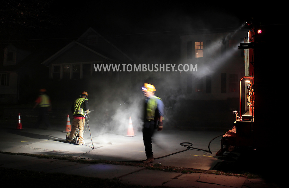 Middletown, New York - An Orange and Rockland Utilities worker cuts into the street while searching for a natural gas leak on the night of March 20, 2012.