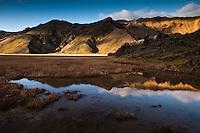 Suðurnámur mountains mirror in a small pond at Laugahraun in Landmannalaugar. Suðurnámur speglast í tjörn við jaðar Laugahrauns í Landmannalaugum. Fallegt kvöldbirta að hausti.