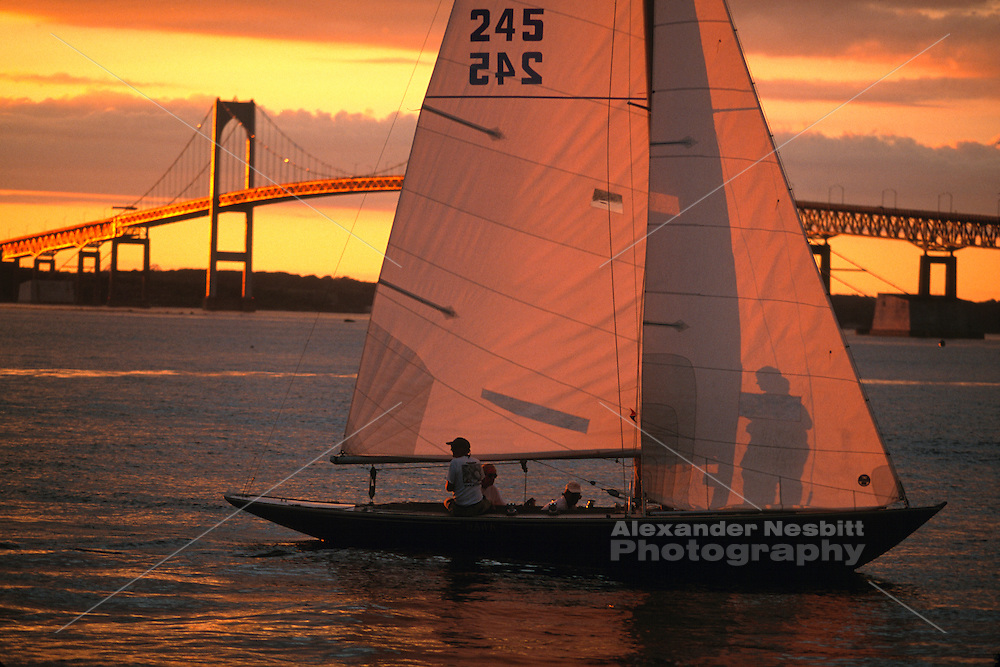 USA,  Newport, RI. Sheild class sailboat coming in from a regatta, sun setting behind Newport Bridge.