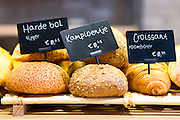Artisan loaves of bread - tiger loaf, croissant and multigrain with euro price tickets in Dutch bakery shop, Holland, The Netherlands