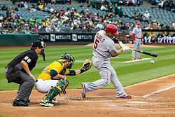 OAKLAND, CA - JUNE 17:  Albert Pujols #5 of the Los Angeles Angels of Anaheim hits a single in front of Stephen Vogt #21 of the Oakland Athletics and umpire Doug Eddings #88  at the Oakland Coliseum on June 17, 2016 in Oakland, California. (Photo by Jason O. Watson/Getty Images) *** Local Caption *** Albert Pujols; Stephen Vogt; umpire Doug Eddings #88