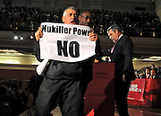 A protester comes holding a banner reading 'Nukiller Power NO' comes within feet of Prime Minister Gordaon Brown as he addresses the Citizens UK General Assembly. He was removed fromt eh stage by a minister before being escorted away by Mr Brown's security. Mr Brown carried on his address throughout the security scare..