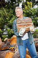 Senior man carrying firewood logs