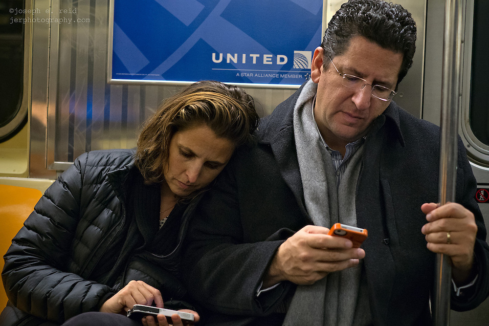 Couple on subway with iPhones.