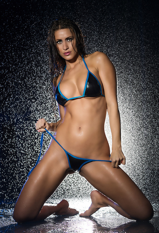 Sensual model in bikini with water behind looking at camera very sensual.