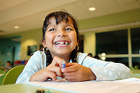 Viviana Reyes, 7, takes a smile break from her homework after school at the César Chávez Library.