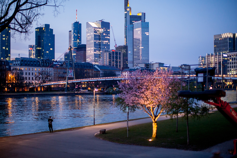 """Germany banned gatherings of more than 2 people called """"social distancing"""" because of the coronavirus. A cyclist and a runner at the shore of river Main in Frankfurt which is very empty on a - normally very busy - Thursday evening."""