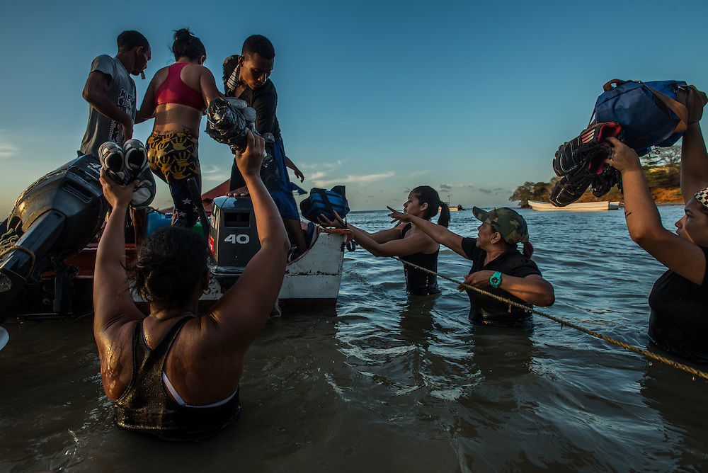 FALCÓN, VENEZUELA - SEPTEMBER 26, 2016: Undocumented migrants, walk into the water to board a smuggler's boat that will illegally take them from Venezuela to Curaçao. Undocumented migrants here have mortgaged property, sold kitchen appliances and even borrowed money from the same smuggling rings that pack them on the floorboards alongside drugs and other contraband. The journey to Curaçao takes them on a 60-mile crossing filled with backbreaking swells, gangs of armed boatmen and coast guard vessels looking to capture migrants and send them home. Then, after being tossed overboard and left to swim ashore, they hide in the brush to meet contacts who spirit them anew into the tourist economy of this Caribbean island. They clean the floors of restaurants, work in construction, sell trinkets on the street, or even solicit Dutch tourists for sex. But at least, the migrants say, there is food. PHOTO: Meridith Kohut for The New York Times