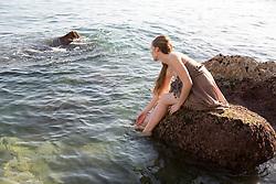 Woman Sitting on Rock in the Sea