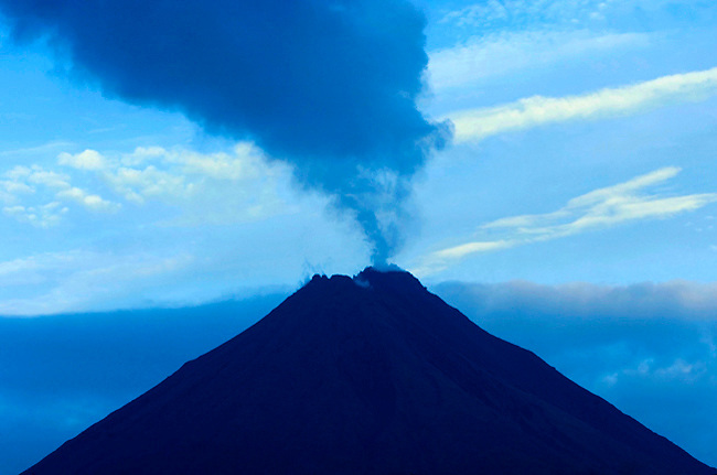 The very active crater of the Arenal Volcano in Costa Rica emits plumes of steam and gas at dawn.