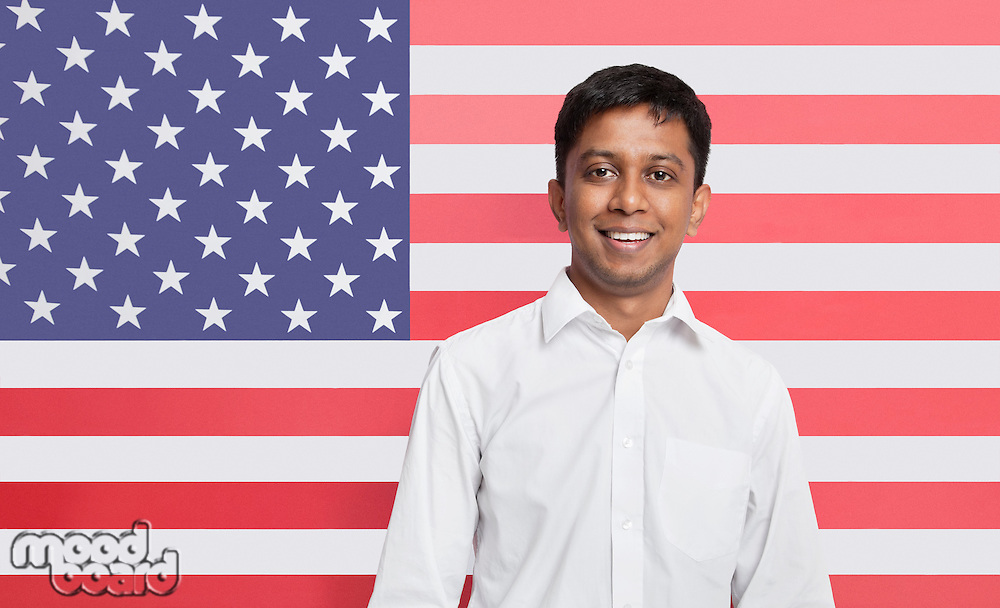Portrait of young Asian man in shirt smiling against American flag