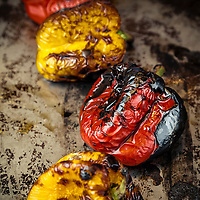 Roasted, blackened red and yellow peppers on a roasting pan.