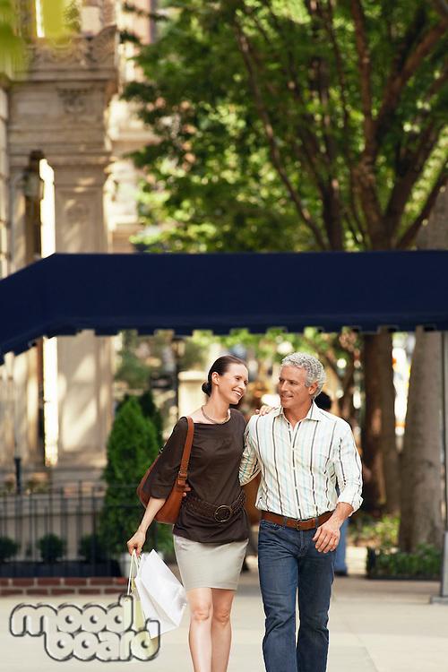Happy couple walking on city street