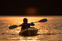 A young boy kayaking in the sunset light at Walden Pond.