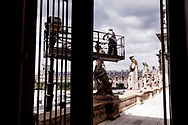 A man is cleaning the outside statues of the Louvre Museum.