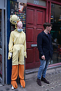 On the day that the UK government warns of 'draconian measures' to help control the spread of Coronavirus, a young man takes a cigarette break in Soho while standing next to a mannequin wearing a surgical mask over its mouth, on 3rd March 2020, in London, England.